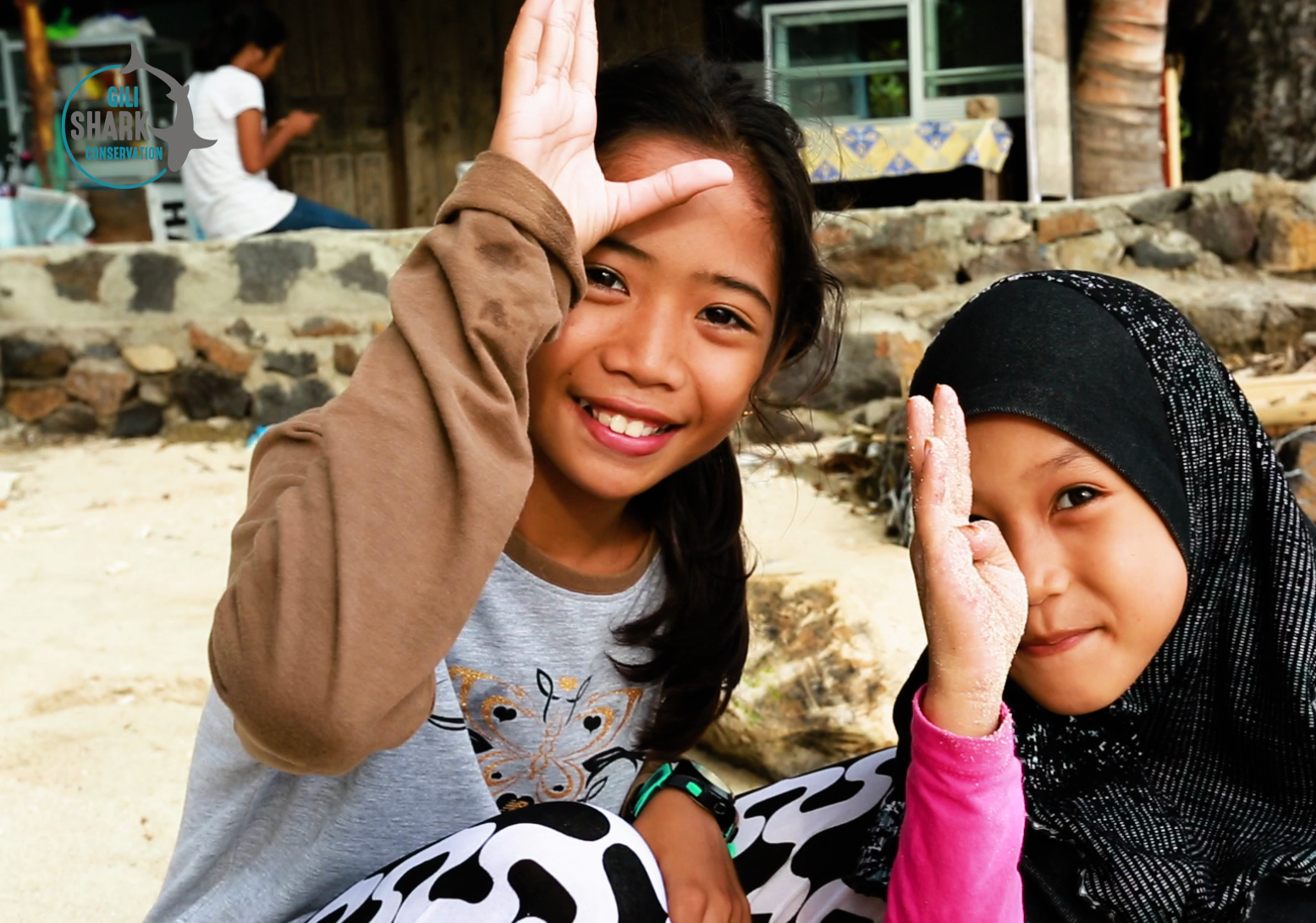 Indonesian kids doing the shark signal