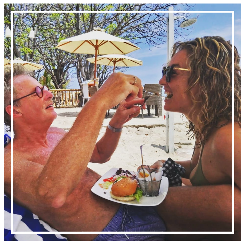 Father and daughter sharing a burger on the beach